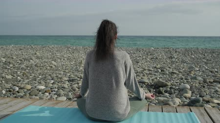 Brunette woman meditating on a beach shore. Stok Video