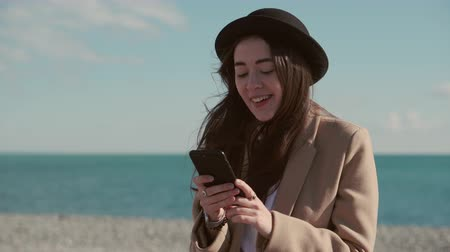 Happy girl on a beach with a phone.