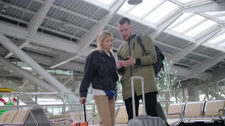 atender : Man and woman with a baggage in airport. Stock Footage