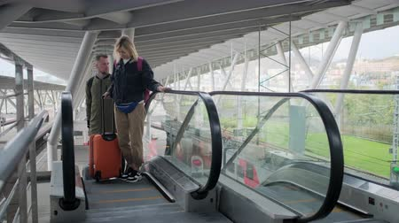 atender : Traveling couple on airport escalator with baggage.