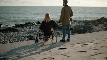 inválido : Woman is sitting in wheelchair on sea coast and holding hand of her husband