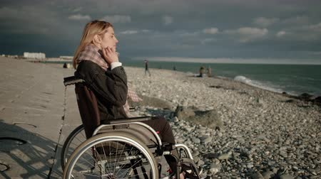 inwalida : Young blonde woman with paralysis of legs is sitting in wheelchair, viewing sea