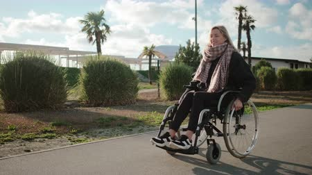 paraplegic : Happy young female wheelchair user is walking in park in sunny day