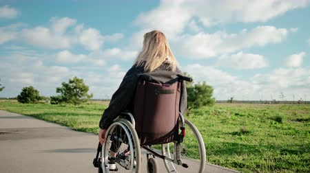 movimentar se : Adult disabled woman is driving her wheelchair in park area in sunny day