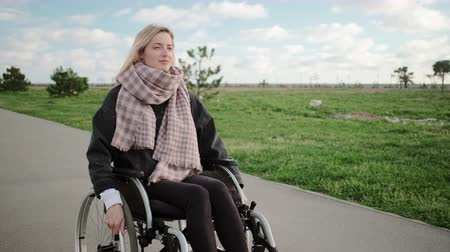 habilidade : Young disabled woman is riding on wheelchair in park area in spring time