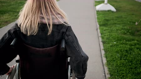 olasılık : Disabled woman is moving in invalid carriage outdoors, close-up of body