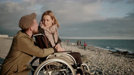 squatting : Female wheelchair user and her boyfriend are chatting and viewing seascape