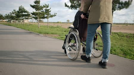 paraplegic : Male is rolling invalid chair with young sick woman outdoors, back and side view