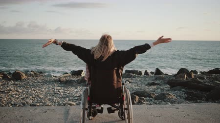 levantado : Alone disabled woman is sitting in wheelchair and holding hands up on sea coast