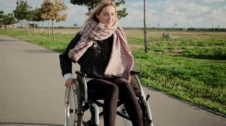 pathology : Cheerful disabled woman is driving her invalid carriage in park, frontal view