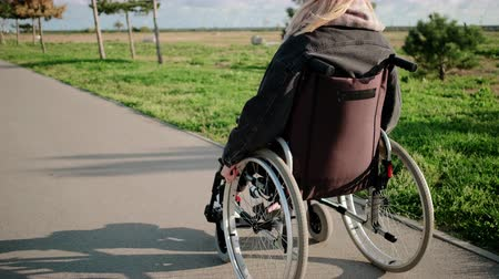 pathology : Young woman is moving by road in park riding invalid chair in sunny weather