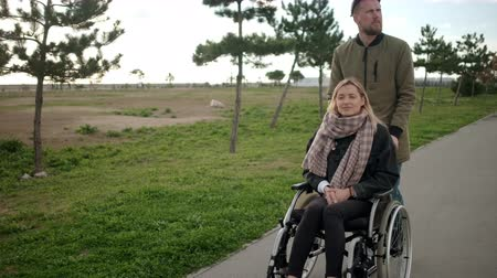 возможность : Young sick woman is sitting in wheelchair, man is helping her and rolling
