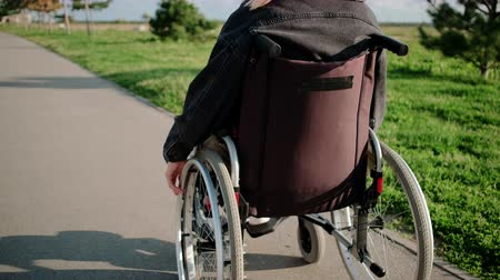 inwalida : Woman is using wheelchair for moving outdoors in sunny day, back view