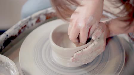 esculpir : Ceramist sculpting clay mug on a wheel.