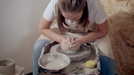 esculpir : Woman molding clay on wheel.