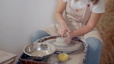 хозяин : Female potter creating a ceramics clay vase.