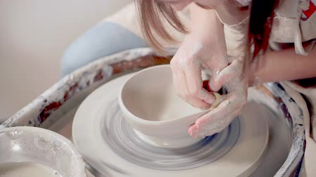 esculpir : Woman does pottery in art studio.