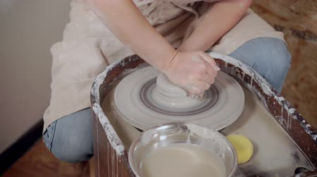 esculpir : Potter molding her clay product on a wheel.
