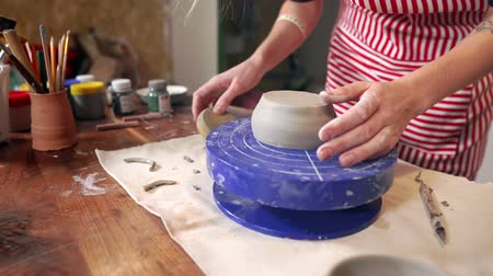 büyücü : Female sculptor is making clay cup in pottery studio, close-up view