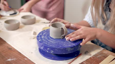 スクレーパー : Woman making a ceramic cup in studio.