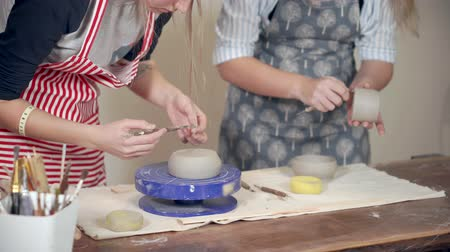 afstemmen : Two female potters are processing ceramic bowls in pottery shop, close-up