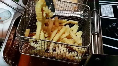 Slow motion of French fries or chips (potato) deep frying in heat oil for a side dish or snack in fastfood restaurant , unhealthy food or fat concept Wideo