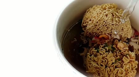 Slow motion of Pour hot water into a instant noodle in white bowl is fastfood and unhealthy food or fat concept
