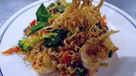 Slow motion of instant noodle mama drunken fried shrimp for sale at Thai street food market or restaurant in Thailand Wideo