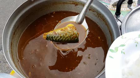çili : Slow motion of Hot spicy curry meat with Thai chili and herb and coconut milk for sale at Thai street food market or restaurant in Thailand