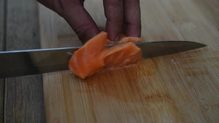 sea piece : Asian chef slice salmon by knife on boad for japanese food delicacy consisting sashimi salmon of very fresh raw salmon fish sliced into thin pieces serving with radish sliced in japanese restaurant