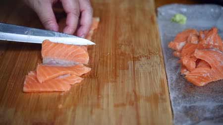 fileto : Asian chef slice salmon by knife on boad for japanese food delicacy consisting sashimi salmon of very fresh raw salmon fish sliced into thin pieces serving with radish sliced in japanese restaurant