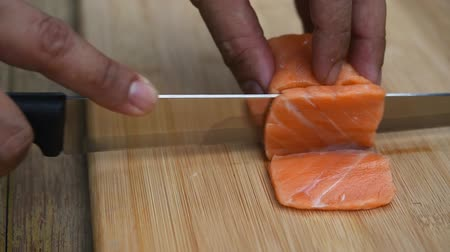 samuraj : Asian chef slice salmon by knife on boad for japanese food delicacy consisting sashimi salmon of very fresh raw salmon fish sliced into thin pieces serving with radish sliced in japanese restaurant