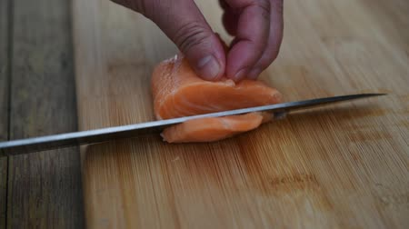 Asian chef slice salmon by knife on boad for japanese food delicacy consisting sashimi salmon of very fresh raw salmon fish sliced into thin pieces serving with radish sliced in japanese restaurant