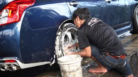 Bangkok, Thailand - December 7, 2018 : Unidentified car care staff cleaning (clean, wash, polish and wax) the car (Car detailing) at car care shop in Bangkok Thailand