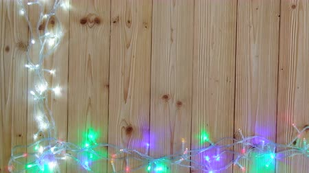dobranoc : Fancy blinker light bulbs or garlands and wreath on wood table for Christmas or New years decoration background, Christmas colorful glowing lights border celebrate with space for add text or picture. 4K, UHD.