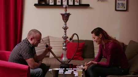 persie : Woman and man smoking hookah and playing board game