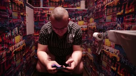 уборная : Man sitting in toilet and playing game on smartphone