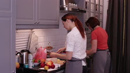 cooks : Women cook in the kitchen. Girl cut apples. Approaching dolly shot on female hands cutting apple in kitchen surrounding