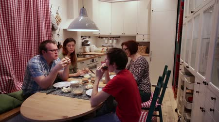porce : People sitting at the kitchen table, eating hamburgers and talking