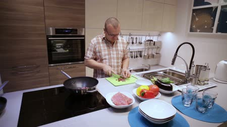 fennel : Cook man cuts the sausages on the Board and lay in pan Stock Footage