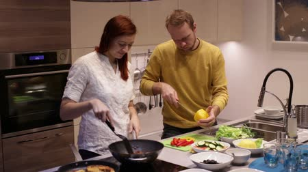 salad : Young couple preparing food in kitchen. The woman at the stove in a pan fry the shrimp. The man with a knife cut the yellow peper on a green chalkboard