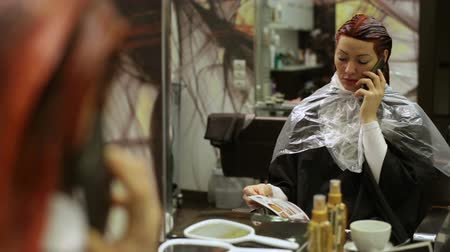 estilista : A woman with dyed hair sitting in a chair in front of a mirror in a beauty salon and talking smartphone