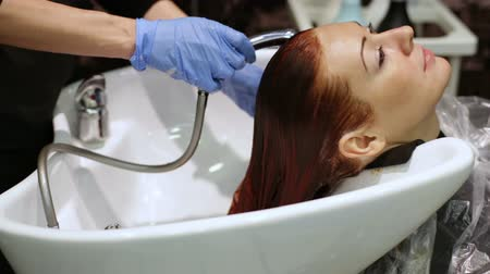 салон : Female hands washing woman hair in sink  Woman leaning head back in sink while male hands rubbing shampoo in hair.