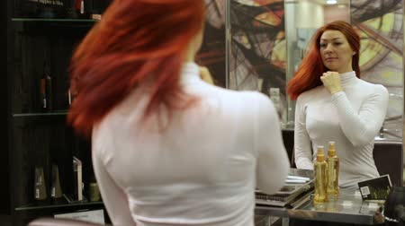салон : Woman in a beauty salon admires her hair in a mirror