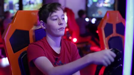 simülasyon : Teenager sits and spins the wheel on the slot machine simulator races
