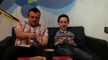 nastolatki : Teenager and boy on Sofa Playing in Computer Game with Joystick