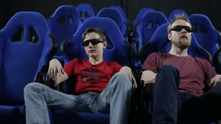 Man father and teenager boy son watching movie in cinema 5d Stock Footage