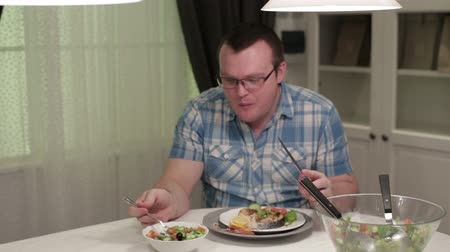 man eating : Young man sitting at a table eating salad Stock Footage