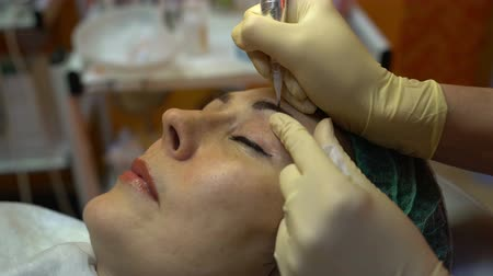 tatuagem : Hands of beautician doing permanent makeup eyebrow Stock Footage