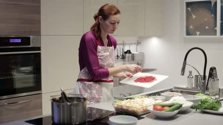 cooks : Woman in kitchen puts chopped tomatoes in the form